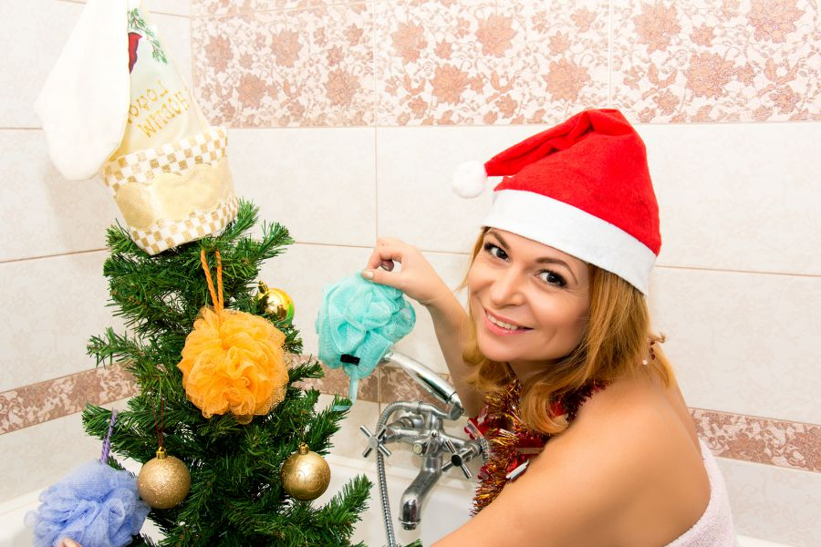 Beautiful woman decorates a Christmas tree in the bathroom.
