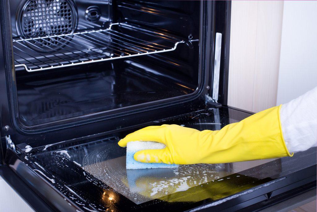 hand cleaning inside of oven door