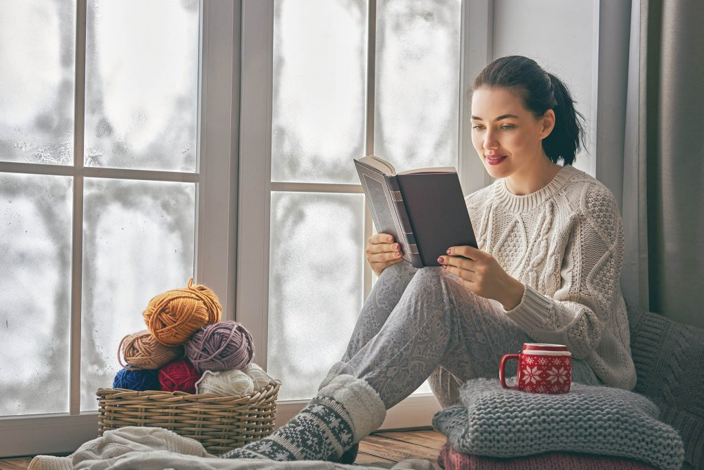 Woman Reading Book in Front of Window