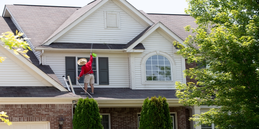 Homeowner washing the exterior of his house standing on the lower roof to spray the second floor facade with a handheld pressure sprayer