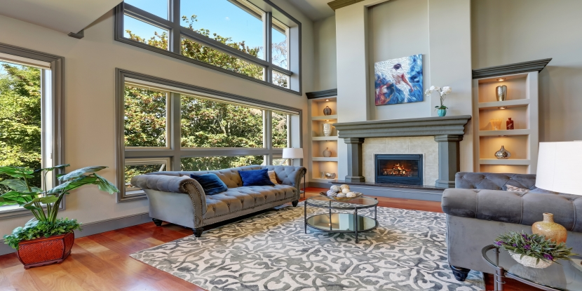 High vaulted ceiling family room in luxury house with fireplace and large windows