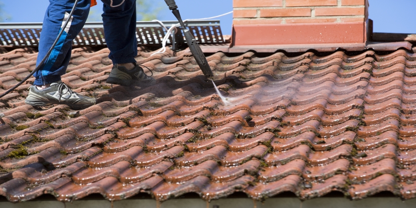 Person pressure washing the roof with a high-pressure water washer machine.