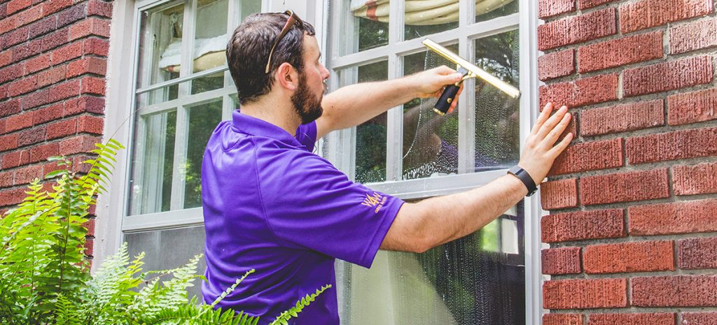 window cleaning service being performed by Window Genie technician