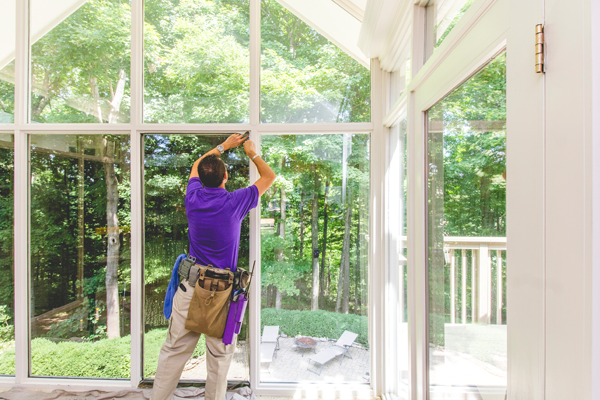 A Window Genie technician installing 3M Envision window film on a home to reduce heat and glare.