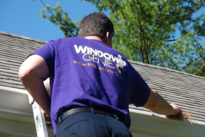 Gutter cleaning service being performed by Window Genie technician