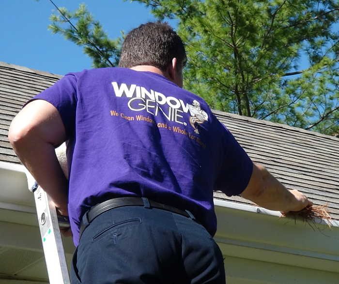 Technician cleaning gutters removing debris from inside the gutter.
